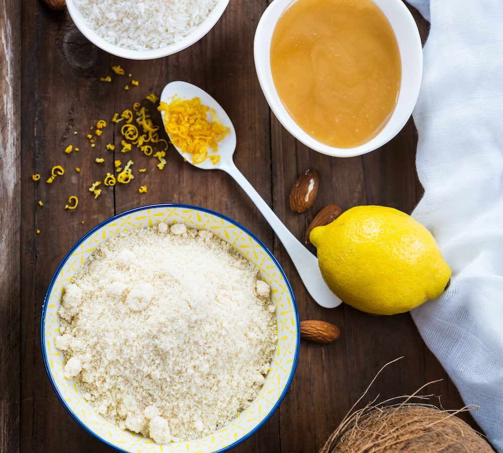 Ingredients for Healthy Vegan Coconut and Lemon Truffles such as Ground Almonds, Desiccated Coconut, Lemon Zest, Honey on Rustic Tray